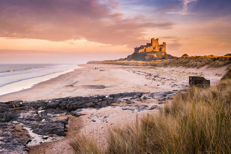 Bamburgh Castle on the Northumberland coastline in late afternoon golden sunlight
